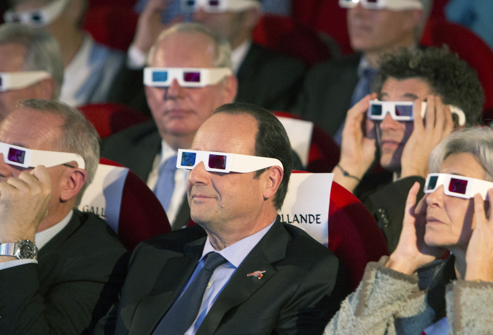 French President Francois Hollande, center, and others wear 3D glasses at a mission broadcast in Paris in 2014. It was a historic first when the Rosetta's lander touched down on comet 67P after a decade-long journey through space.