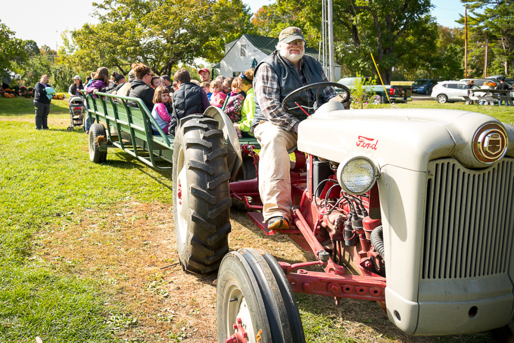 Driver Doug McDougal, of The Apple Farm in Fairfield, begins a hayride taking children and adults around the farm. McDougal pointed out various varieties of apple trees while on the tour.