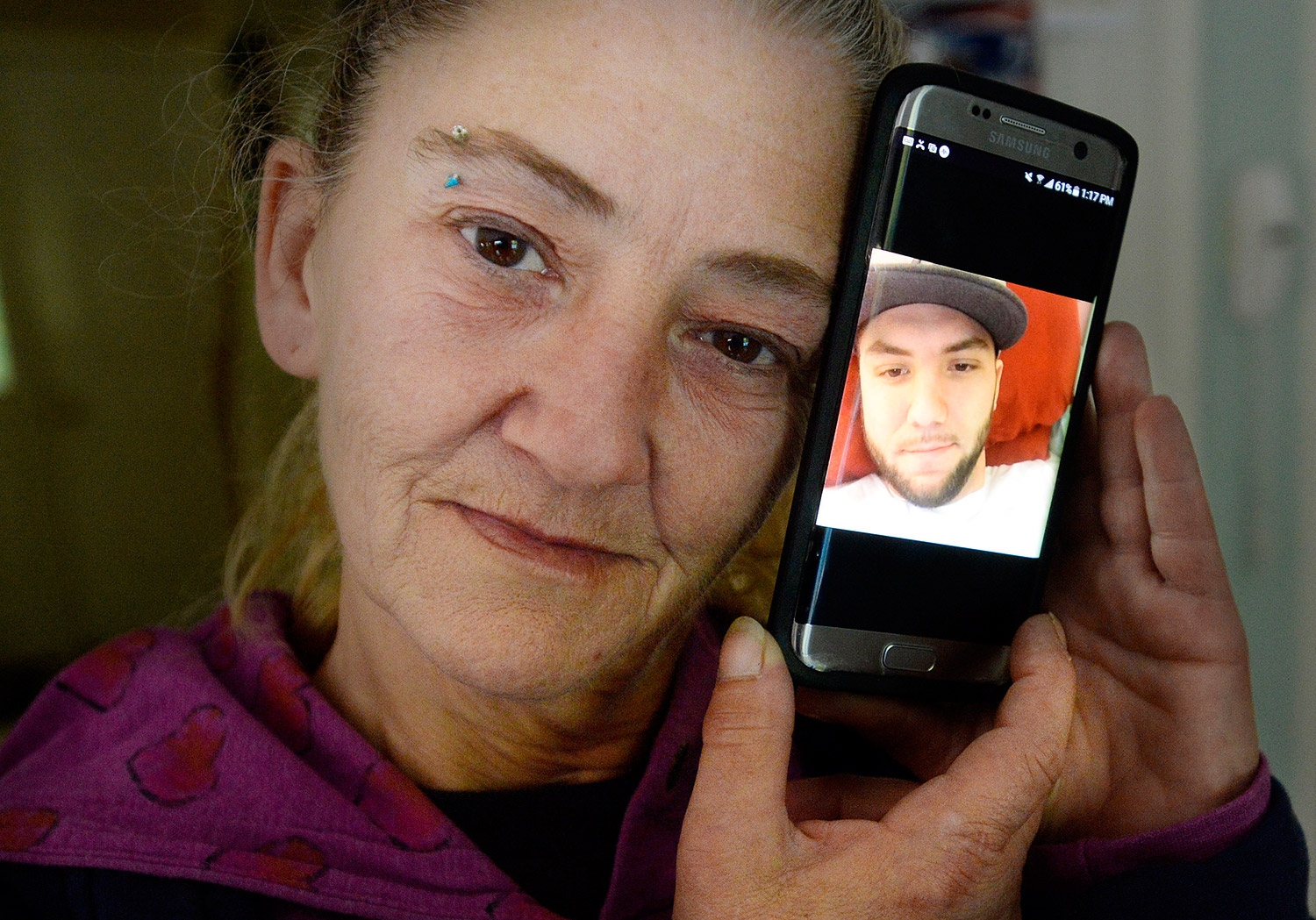 """Cheryl Methot, the mother of Jonathon Methot, who was shot early Monday morning in Biddeford, holds a phone with a photo of her son Friday. She said her son had struggled with prescription opiate addiction, but was working to get his life back on track, and """"was doing really good."""" Shawn Patrick Ouellette/Staff Photographer"""