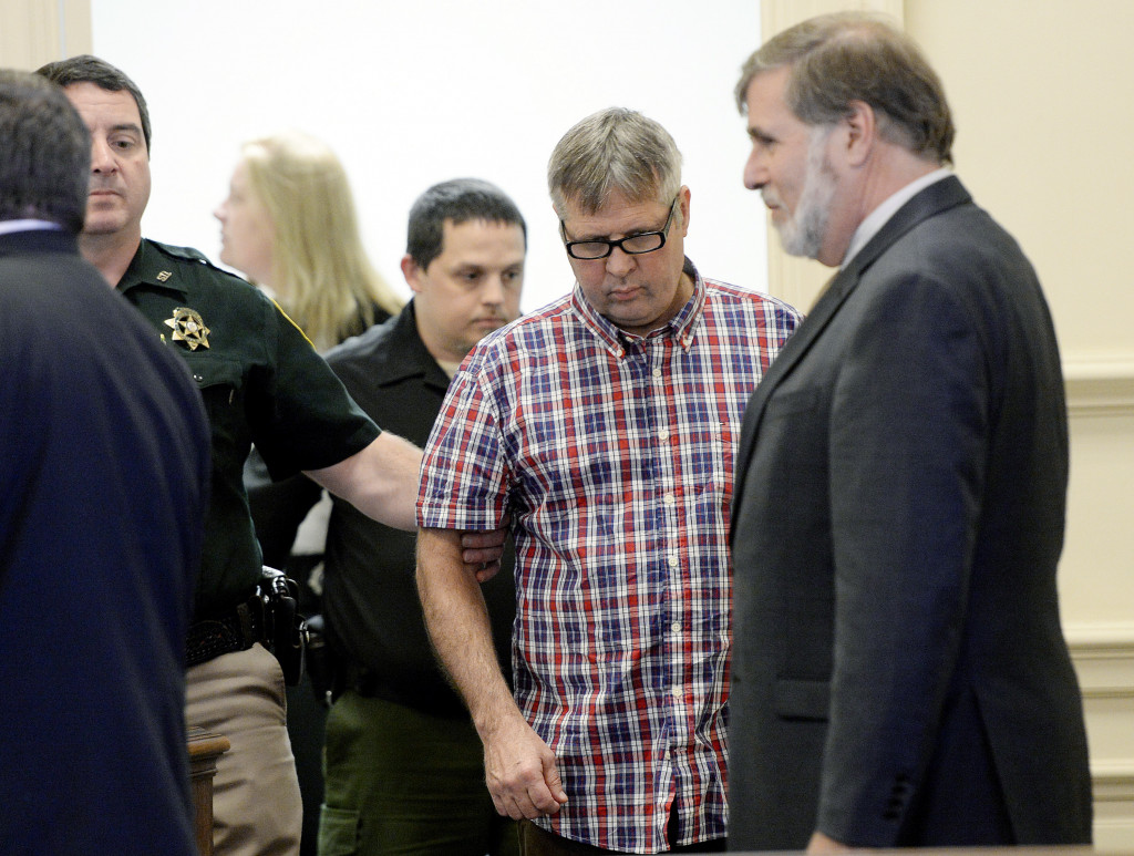 Bruce Akers, who is accused of killing of his neighbor with a machete, is led into the York County Superior Court in Alfred, where he pleaded not guilty on Tuesday.