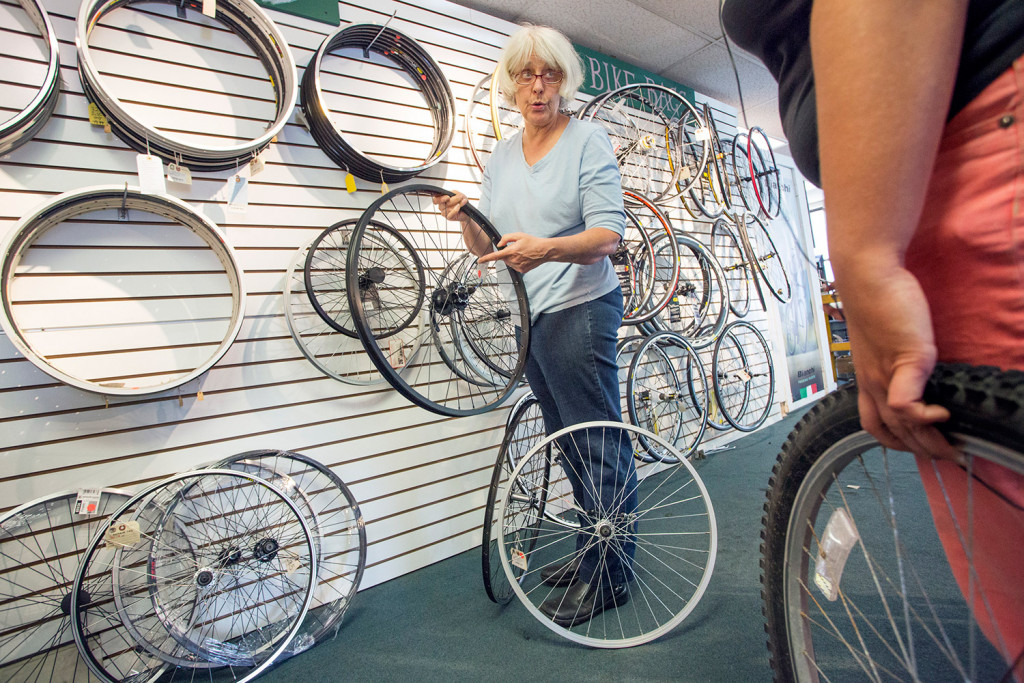 Back Bay Bicycle's owner, Cheryl Oliver, helps a customer find a wheel for her bike Tuesday. Oliver says she's closing because she didn't want to sign another long-term lease or move the store.