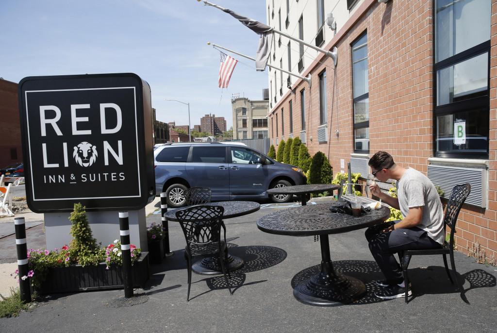 Gary Cornish eats his habitual breakfast, a sandwich and an iced coffee from the corner deli, in the parking lot of the Red Lion Inn & Suites in New York where he and the other members of his team stay when the team is not traveling. Associated Press/Kathy Willens