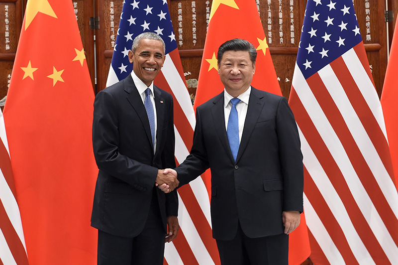 Presidents Obama and Xi Jinping pose for photographers as they shake hands before their meeting in Hangzhou.