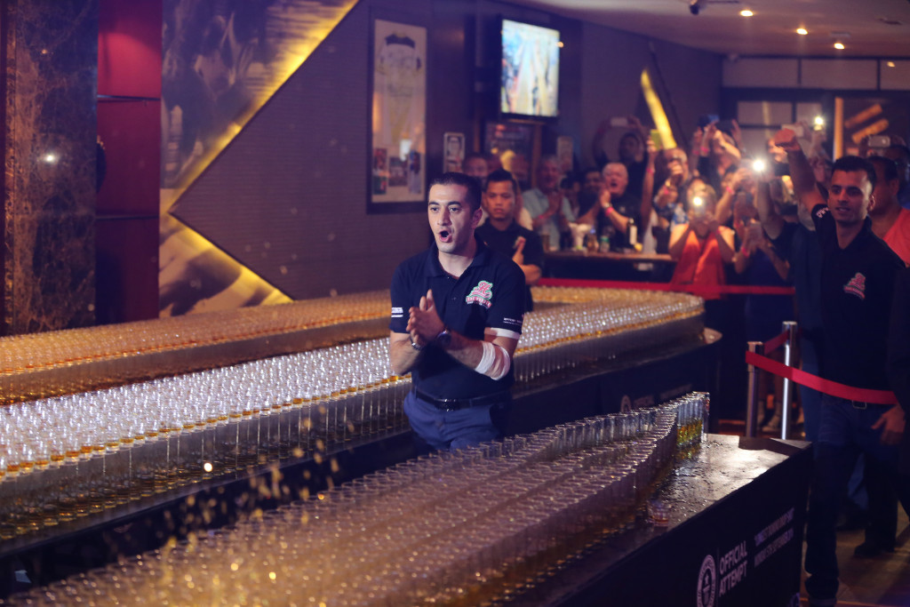 Ahmad Taher pushes over a shot glass in a successful attempt at the world's longest domino drop shot.    Associated Press/Kamran Jebreili