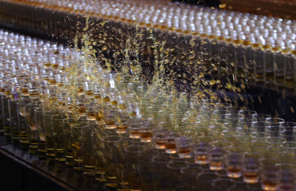 Shot glasses drop over each other during a successful attempt to break the world's longest domino drop shot.   Associated Press/Kamran Jebreili