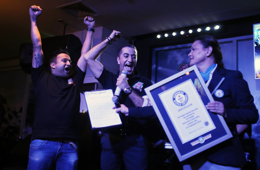 Ahmad Taher, food and beverage manager for Citymax Hotels in Dubai, middle, celebrates with his crew after he won the attempt of world's longest domino drop shot Monday.    Associated Press/Kamran Jebreili