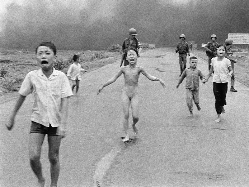 The  June 8, 1972 file photo of South Vietnamese forces following terrified children, including 9-year-old Kim Phuc, center, as they run near Trang Bang after an aerial napalm attack.