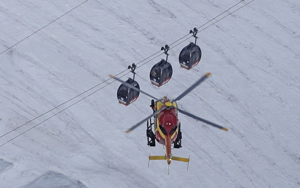 A helicopter operated by the French Societe' Civile hovers Friday near cable cars  that stalled around 4 p.m.  Thursday when the cables reportedly tangled. <em>Luca Bruno/Associated Press</em>
