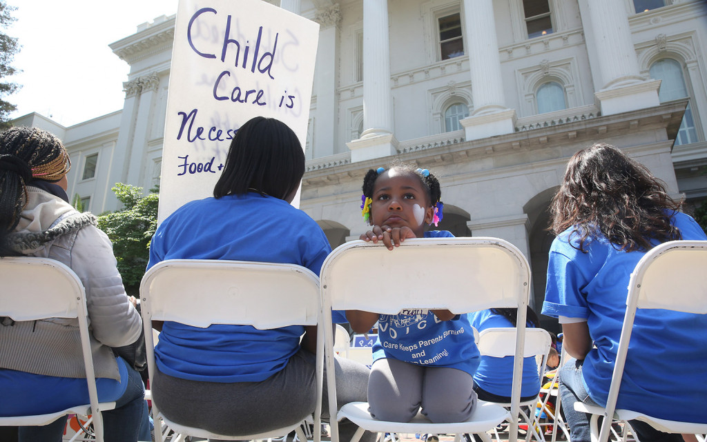 Saryah Mitchell sits with her mother, Teisa, Gay, left, a 2015 rally calling for increased child care subsidies at the Capitol in Sacramento, Calif. In much of the U.S., families spend more on child care for two kids than on housing.