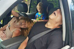 The East Liverpool , Ohio, Police Department, posted this Sept. 7, 2016, photo of a young boy sitting in a vehicle behind his grandmother and her boyfriend, both of whom are unconscious from a drug overdose. Police photo via Associated Press