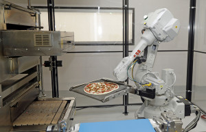 A robot places a pizza into an oven at Zume Pizza in Mountain View, Calif., recently. The startup, which began delivery in April, is one of a growing number of food-tech firms seeking to disrupt the restaurant industry. Marcio Jose Sanchez/Associated Press