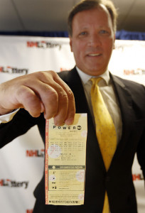 Charlie McIntyre, executive director of the New Hampshire Lottery Commission, holds the winning $487 million Powerball ticket from the July 30 drawing during a news conference Monday in Concord, N.H. Jim Cole/Associated Press
