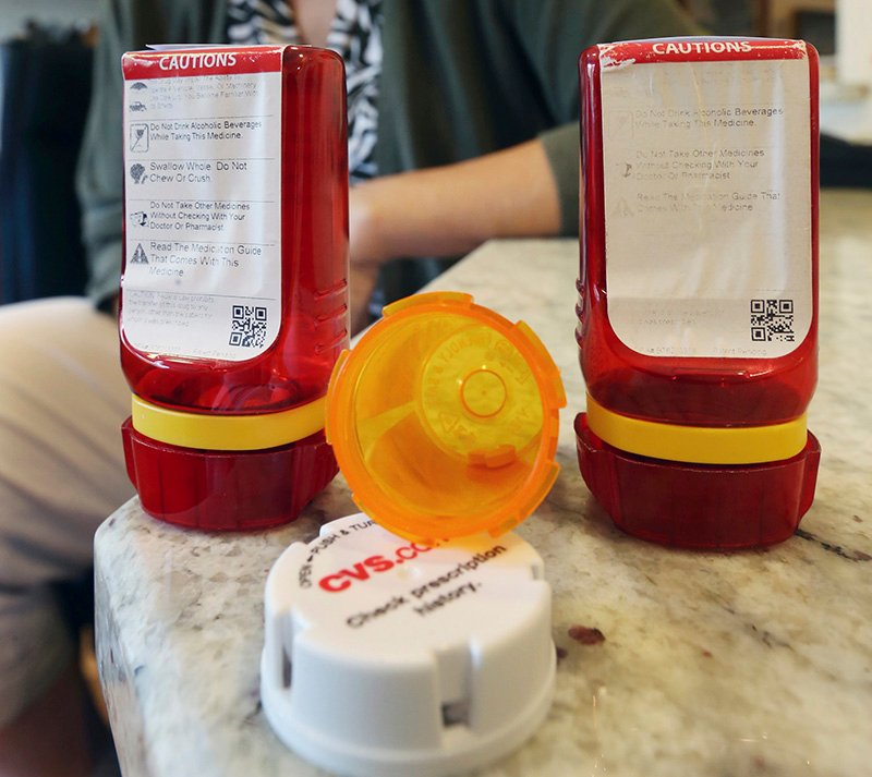 An open, amber-colored CVS pharmacy bottle lies between two of the innovative red ones that Target used before CVS took over operation of Target's drugstores earlier this year. Mel Evans/Associated Press