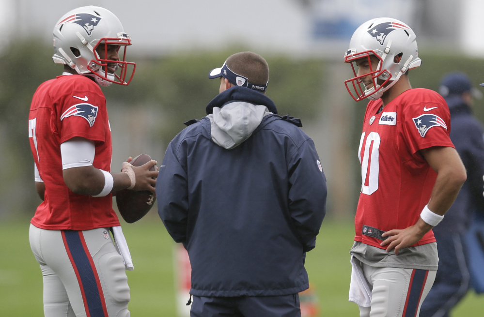 Patriots quarterbacks Jacoby Brissett, left, and Jimmy Garoppolo speak with offensive coordinator Josh McDaniels during practice Wednesday. Both players are dealing with injuries, and the Patriots haven't announced a starter.