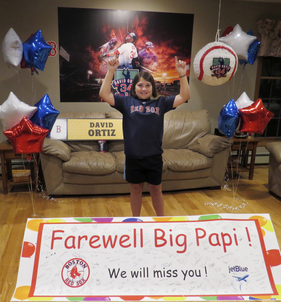 Caitlin Cunliffe points skyward, just like David Ortiz after a home run, as the 11-year-old from Minot poses with a farewell card put together with her father, Dan Cunliffe II, and signed by folks from all over Maine.