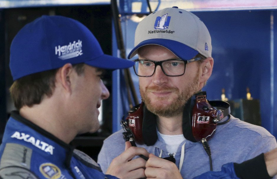 Dale Earnhardt Jr., right, who is recovering from a concussion, listens to Jeff Gordon  as they stand in the garage area before practice for Sunday's Sprint Cup race at Dover International Speedway. Gordon came out of retirement to fill in for the injured Earnhardt.