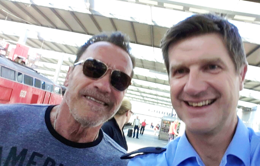 Arnold Schwarzenegger poses with police Officer Stefan Schmitt for a selfie in a Munich, Germany, train station.