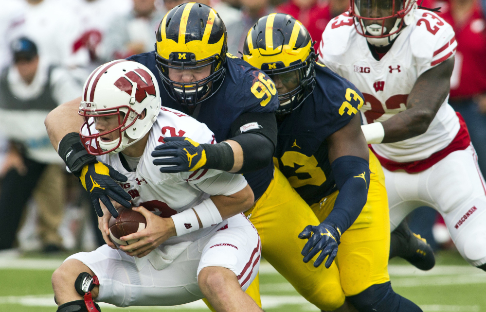 Wisconsin quarterback Alex Hornibrook is sacked by Michigan defensive tackle Ryan Glasgow, center, and Taco Charlton, 33, in the second quarter of Saturday's Big Ten game in Ann Arbor, Mich., won by the Wolverines.