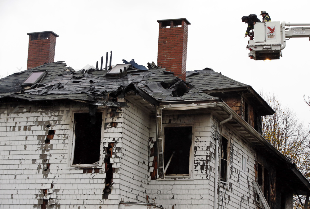 Firefighters examine the charred apartment building at 20-24 Noyes St. in Portland after the fire on Nov. 1, 2014.