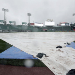 A tarp covers the infield at Fenway Park during steady rain before Game 3 of baseball's American League Division Series between the Cleveland Indians and the Boston Red Sox Sunday in Boston. The game was postponed until Monday.