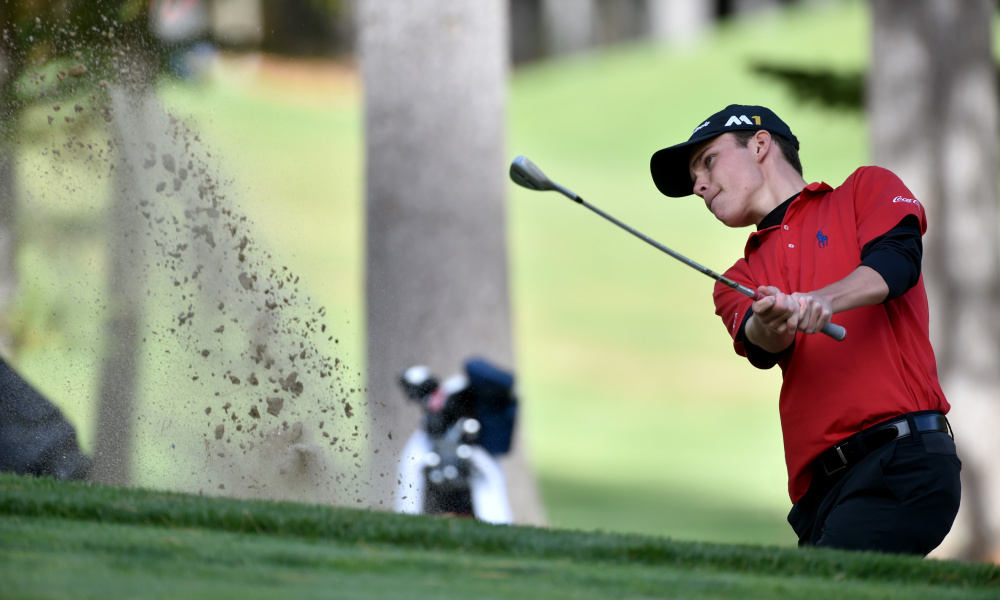Cole Anderson of Camden Hills chips out of a sand trap on the 15th hole during the high school individual golf championships Saturday at Natanis Golf Course in Vassalboro. Anderson shot 1-over 73 to win the Class A title for the second year in a row.