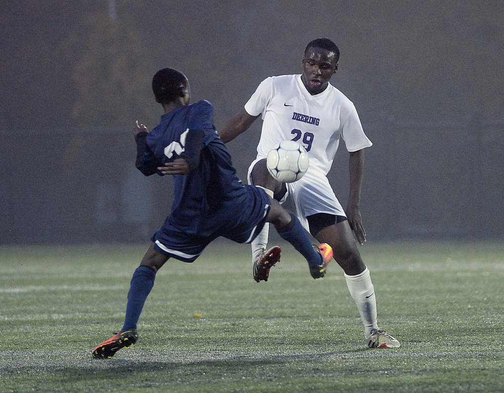 Portland's Samuel Nkurunziza, left, battles for the ball with Jonata Mbongo of Deering on Tuesday.