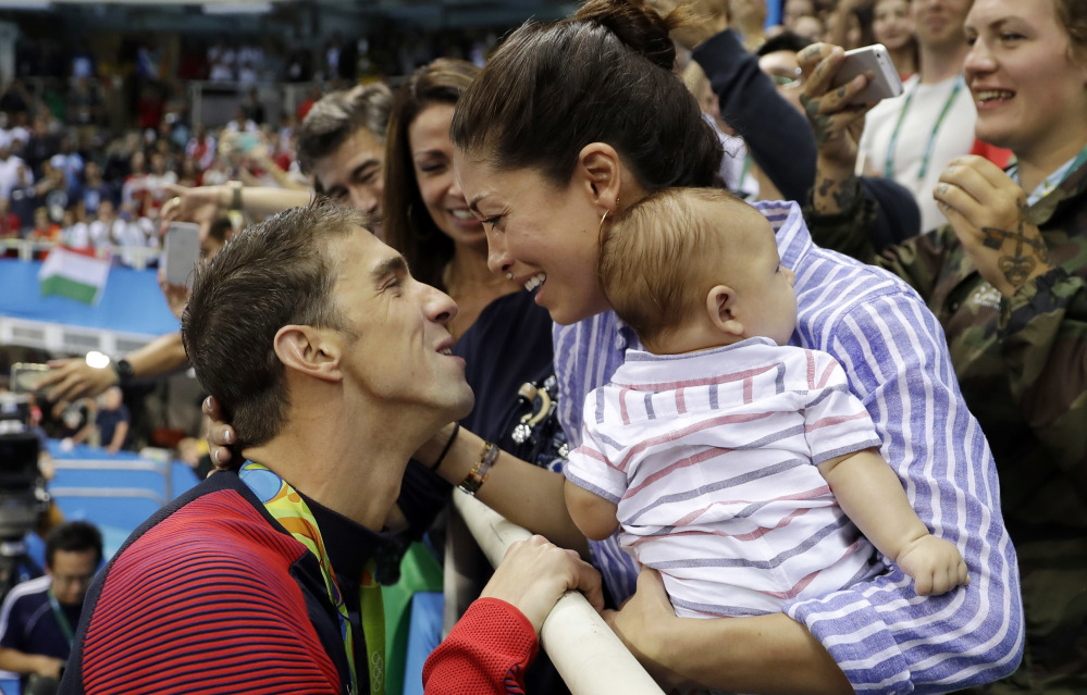 Swimmer Michael Phelps celebrates winning his gold medal in the men's 200-meter butterfly with Nicole Johnson and baby Boomer during the Rio Olympics.
