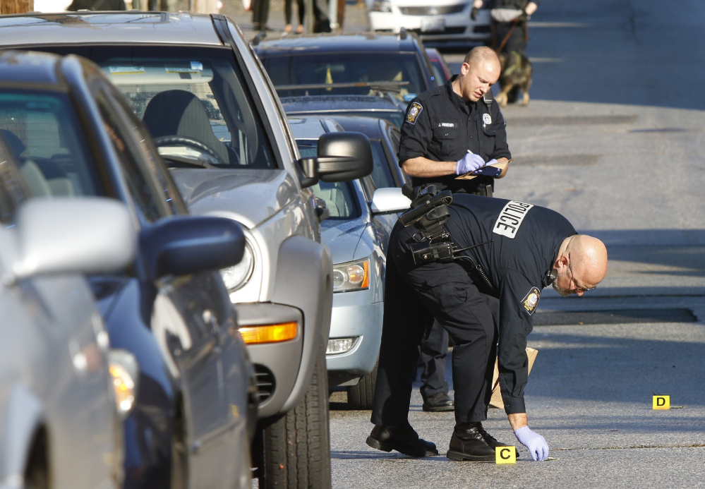 Portland police Evidence Technician Chris Stearns picks up a dollar bill on Gilman Street while documenting evidence at the scene where shots were fired on Wednesday, Oct.19.