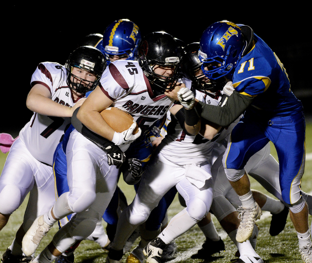 Greely's Tim Coyle looks for running room and gets a push from a teammate as Falmouth's Griffin Aube moves in for the tackle during their Class B South quarterfinal Friday night in Falmouth. After losing to the Yachtsmen a week earlier, Greely advanced to the semifinals with a 20-7 win.