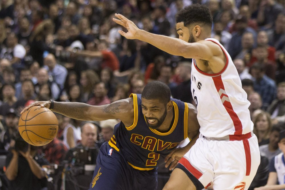 Cleveland's Kyrie Irving, left, drives on Toronto's Cory Joseph during the second half of a 94-91 win by the Cavaliers at Toronto on Friday. Irving led the Cavaliers with 26 points.