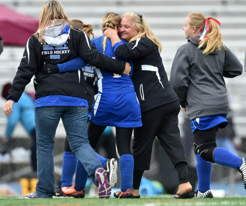 Betsy Gilbert, second from right, coach of the Oak Hill field hockey team, embraces Erika Hannifin (1) after the Raiders beat Maine Central Institute 2-0 for the Class C state championship in Bath on Saturday.