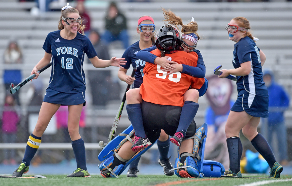 York High's Sydney Bouchard jumps in to the arms of goalie Julia Carr after the Wildcats defeated Belfast, 2-1, in the Class B field hockey state championship game in Bath on Saturday.