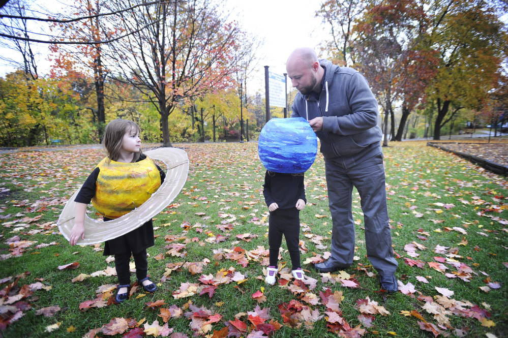 Dressed as the planet Saturn, Leah Purinton, 5, of Naples watches as her father, Stewart Purinton, helps Lydia Purinton, 2, with her Neptune costume on Friday. Data shows kids pick Halloween costumes based on hopes and dreams, but adults pick based on fear.