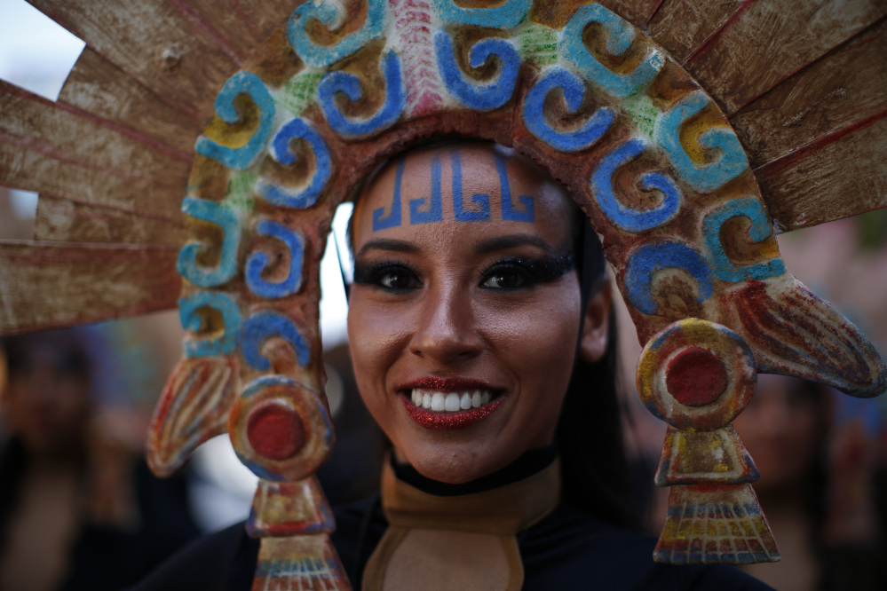 A woman in costume smiles as she waits for the start of a Day of the Dead parade to begin in Mexico City on Saturday (AP Photo/Dario Lopez-Mills)