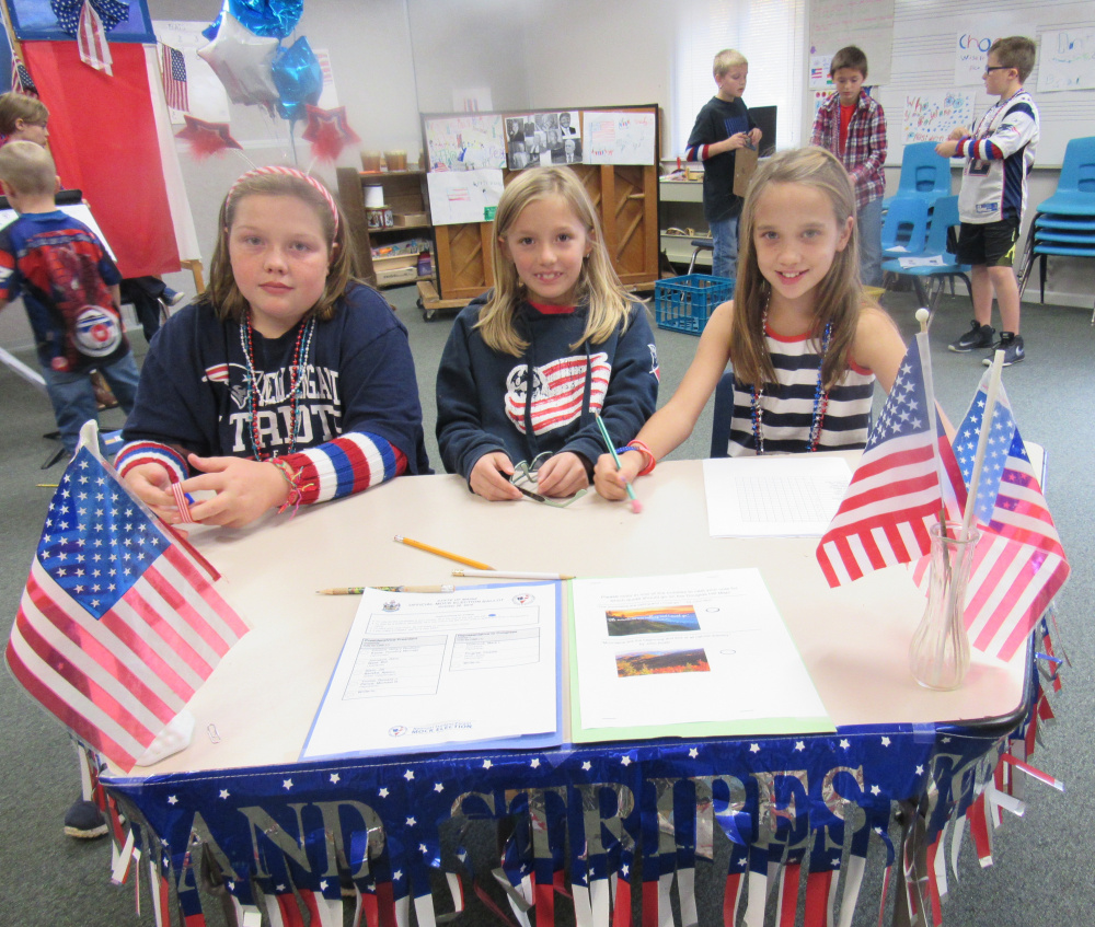 Sebago Elementary School students, from left, Emma McKenney, Averie Smith and Madyson Lantz man a voter registration table during a recent mock election at the school. All three are in the fourth grade. Students in third through fifth grades helped in the voter education process, performing skits for kindergarten through second grade  students, helping teach about the election and the process of voting. Later, the students voted on the candidates for president and the Senate.