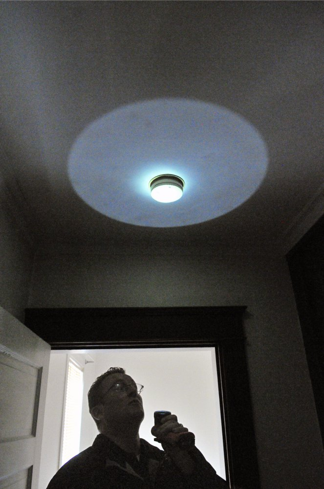 City of Augusta Code Enforcement Officer Robert Overton points a flashlight at a smoke alarm during an Oct. 2 inspection of an apartment building.