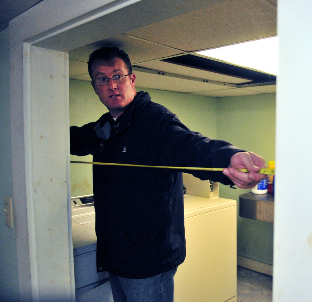City of Augusta Code Enforcement Officer Robert Overton measures a doorway during an Oct. 2 inspection of an apartment building.