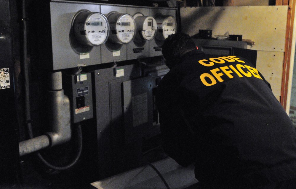 City of Augusta Code Enforcement Officer Robert Overton checks out an electrical system during an Oct. 2 inspection of an apartment building.