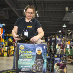"""Tina Currie prepares a costume for display at Spirit Halloween in South Portland. """"It's always busy here,"""" she said. """"It's just 'go, go, go.'"""""""