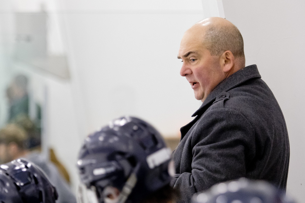 Jeffrey Beaney, coaching the Portland/Deering high school hockey team, speaks with his players during a game in December 2015. Beaney was USM's coach for nearly three decades.