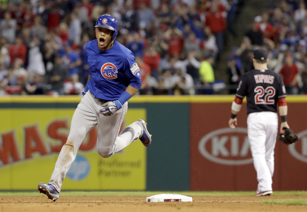 The Cubs' Addison Russell celebrates his grand slam home run in the third inning of Game 6 on Tuesday night in Cleveland. Russell provided the offensive power in the Cubs' series-evening win over the Indians.