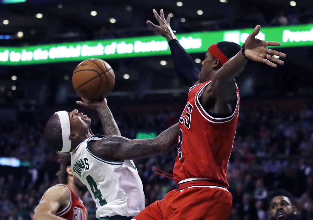 Chicago's Rajon Rondo, right, blocks a shot by Boston's Isaiah Thomas in the first quarter Wednesday night in Boston.
