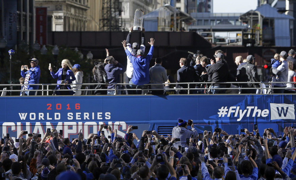 Chicago Cubs' Dexter Fowler hoists the championship trophy during a parade honoring the World Series champion Chicago Cubs baseball team on Friday in Chicago.