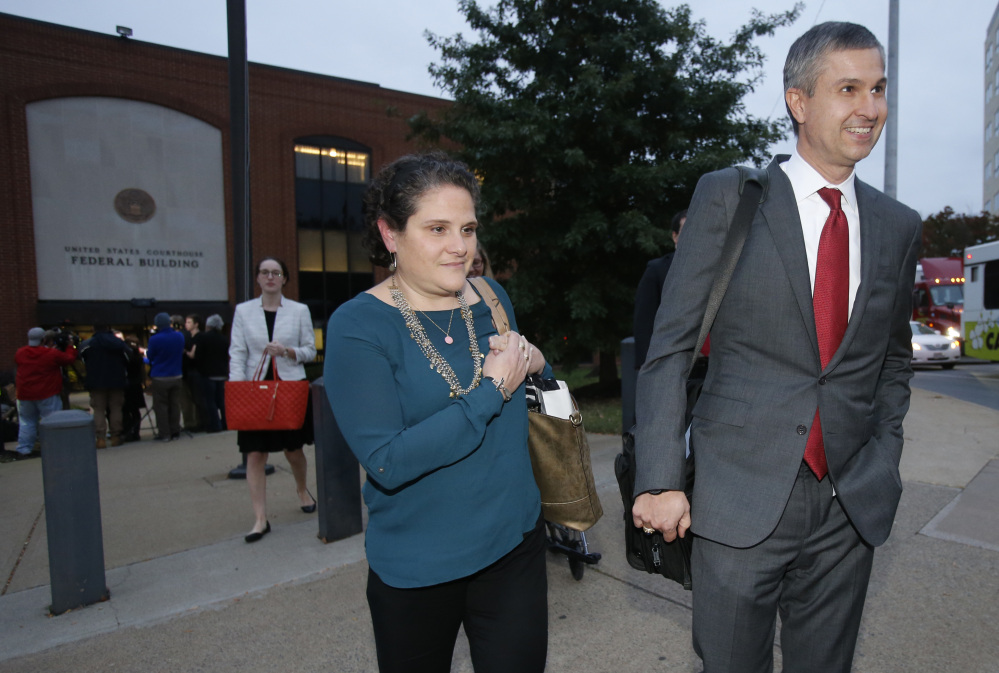 University of Virginia administrator Nicole Eramo, center, leaves federal court with her attorney Tom Clare, right, after closing arguments in her defamation lawsuit against Rolling Stone magazine in Charlottesville, Va. A jury Friday ruled against the magazine.