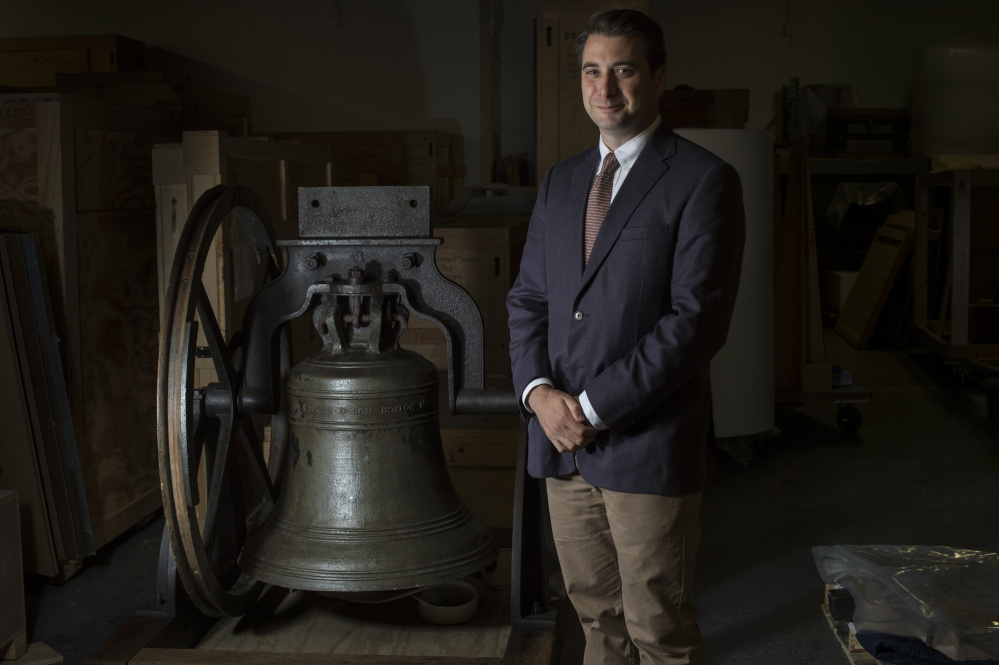 Religion curator Peter Manseau poses for a portrait near a church bell made by Paul Revere at the Smithsonian National Museum of American History in Washington.