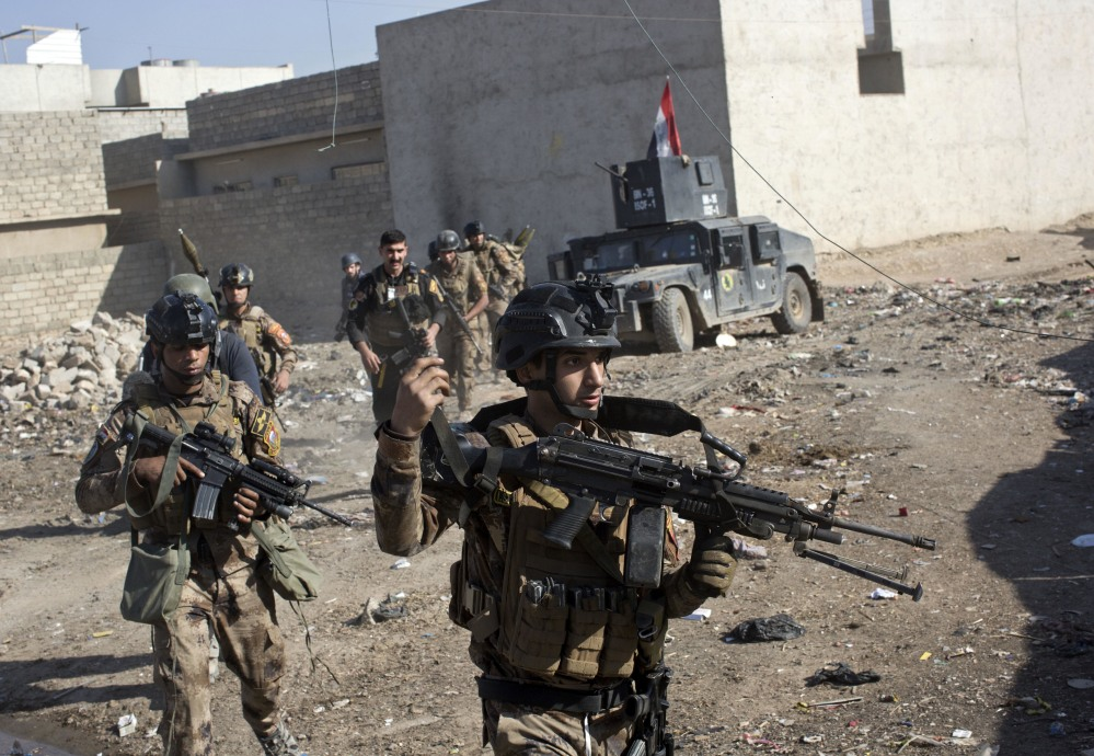 Iraqi special forces soldiers move in formation in an alley on the outskirts of Mosul, Iraq, on Friday. A two-pronged assault against Islamic State militants involved more than 3,000 Iraqi troops and unleashed intense street battles. At one point, seven suicide attackers barreled in vehicles laden with explosives toward the troops.