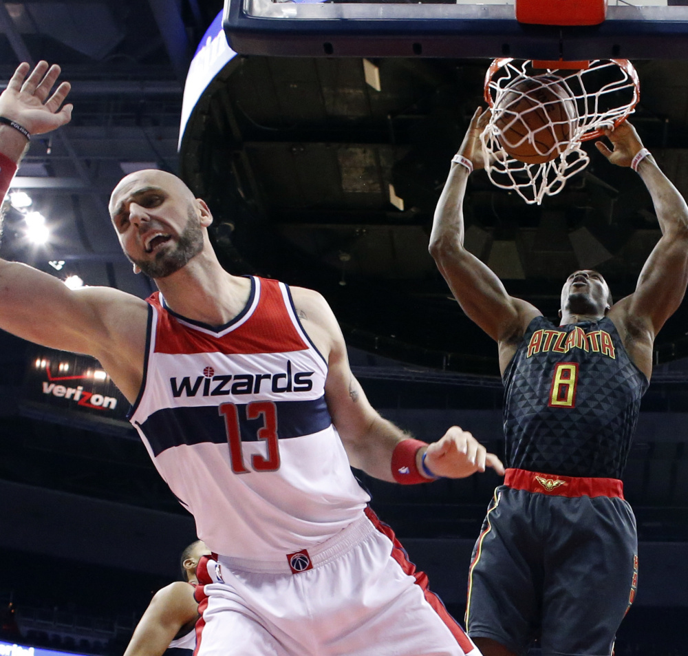 Wizards center Marcin Gortat can't stop a dunk from Hawks center Dwight Howard during the first half of their game in Washington on Friday. The Wizards won 95-92.