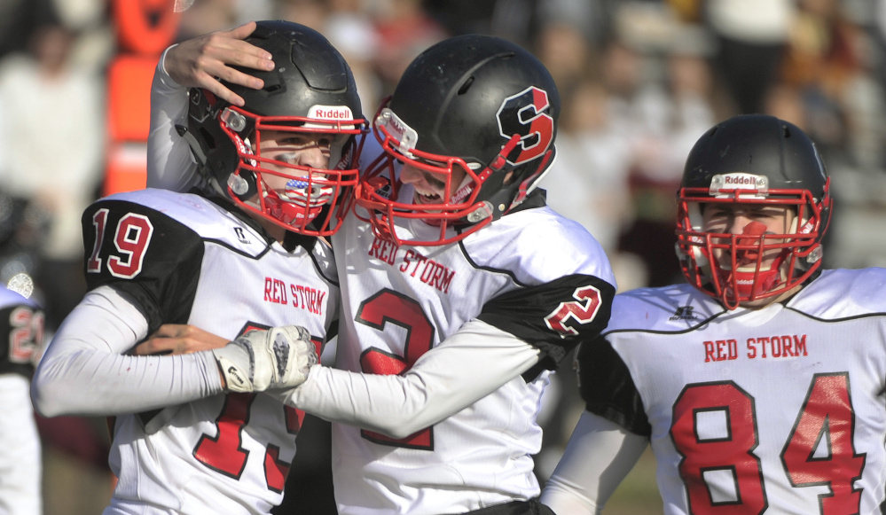 Scarborough's Eric Quirk, left, is congratulated by Emmett Peoples, center, and Jared Quintiliani following his fourth-quarter touchdown to give Scarborough a 28-21. Scarborough went on to a 36-29 win.