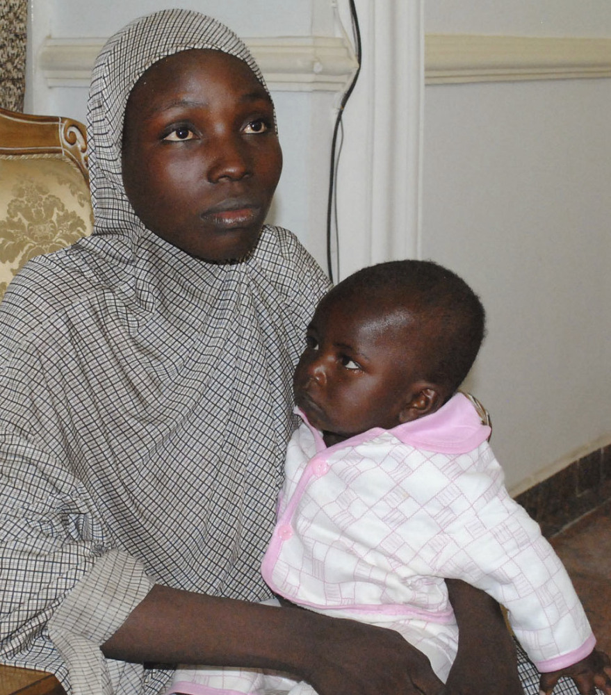 A rescued Chibok girl holds the 10-month-old boy whom she had with a Boko Haram fighter.