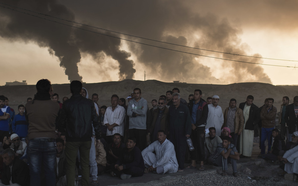 Men are held by Iraqi national security agents, to be interrogated at a checkpoint as oil fields burn in Qayara, south of Mosul, Iraq, on Saturday.